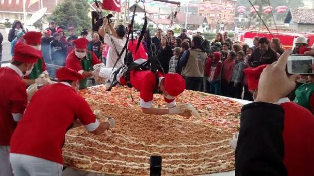 Um pizzaiolo precisou ser suspenso sobre a pizza para alcançar o meio da massa gigante e colocar o recheio / Foto: RankBrasil