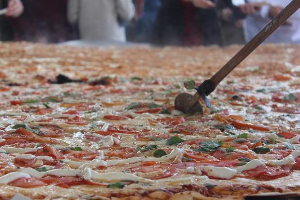 Com 3,11 m de diâmetro e 156,11kg, a pizza gigante foi servida para crianças da rede municipal de ensino / Foto: RankBrasil