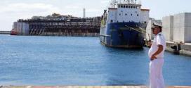 Oficial da Guarda Costeira italiana fala em seu rádio enquanto o navio chega ao porto de Génova, no norte da Itália