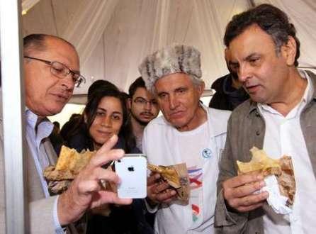 Geraldo Alckmin (esq), o padre Rosalvino Morán (centro) e Aécio Neves comem pastel na Feira Tecnológica