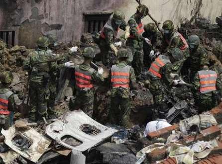 Oficiais observam destroços do avião que caiu em Taiwan na última quinta-feira