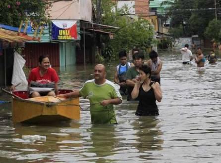 Moradores usam um pequeno barco para o transporte de uma mulher por uma rua inundada após a tempestade tropical Fung-Wong, na província de Rizal, a leste de Manila, em 20 de setembro