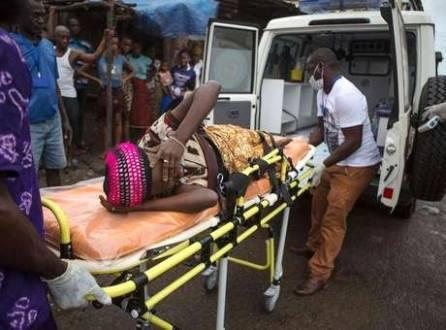 Mulher grávida com suspeita de estar com ebola é levada para ambulância em Freetown