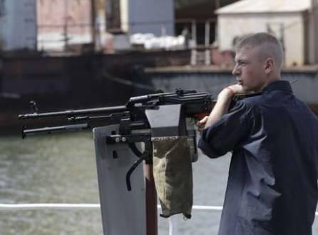 Soldado ucraniano fica ao lado de arma no porto de Mariupol