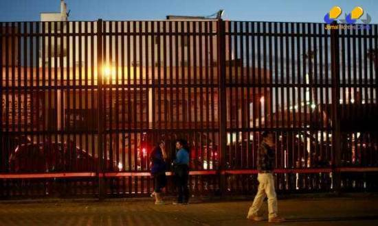 Pessoas em frente à fronteira dos EUA com o México, na cidade de Caléxico, California