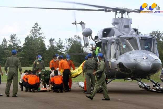 Corpos de vítimas da queda do avião da AirAsia são retirados de helicóptero nesta quinta-feira (22) em Pangkalan Bun, na Indonésia; eles foram encontrados perto da fuselagem da aeronave, no fundo do mar (Foto: Yudha Manx/AFP)