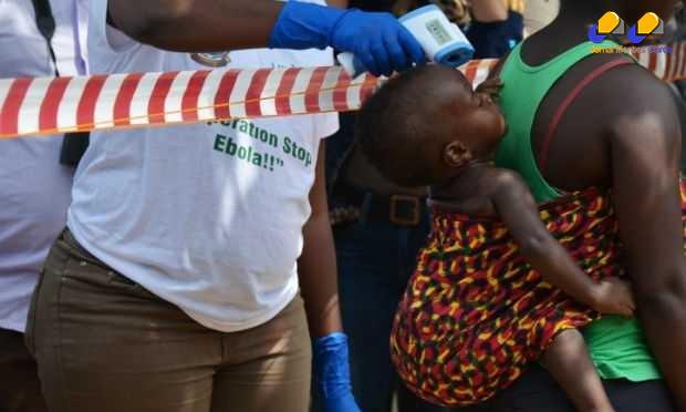 Na imagem, agente de saúde verifica temperatura de criança. Um dos sintomas da doença é febre