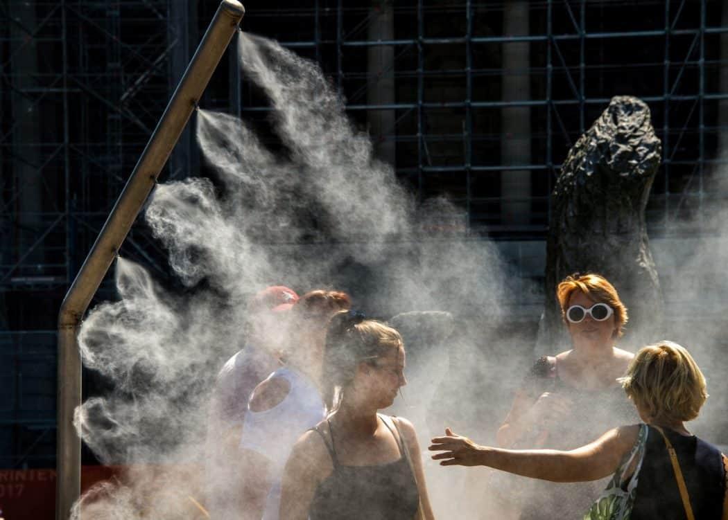 Mulheres se refrescam com borrifador de água público em Lille, na França, durante onda de calor no verão deste ano — Foto: Philippe Huguen/AFP