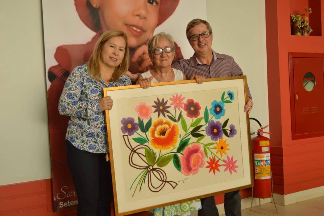 Entre os representantes da Fundação Sara (Álvaro e Marlene), Dona Adelícia exibe a obra que doou à entidade.